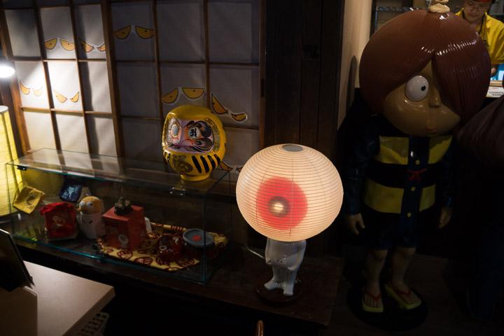 茶屋のレジ前に、光る目玉のおやじと暗がりの鬼太郎。だるまが阪神タイガースカラー(違